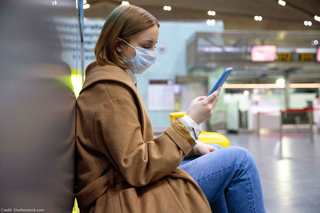A woman wearing a face mask sits at an airport while scrolling through her phone.