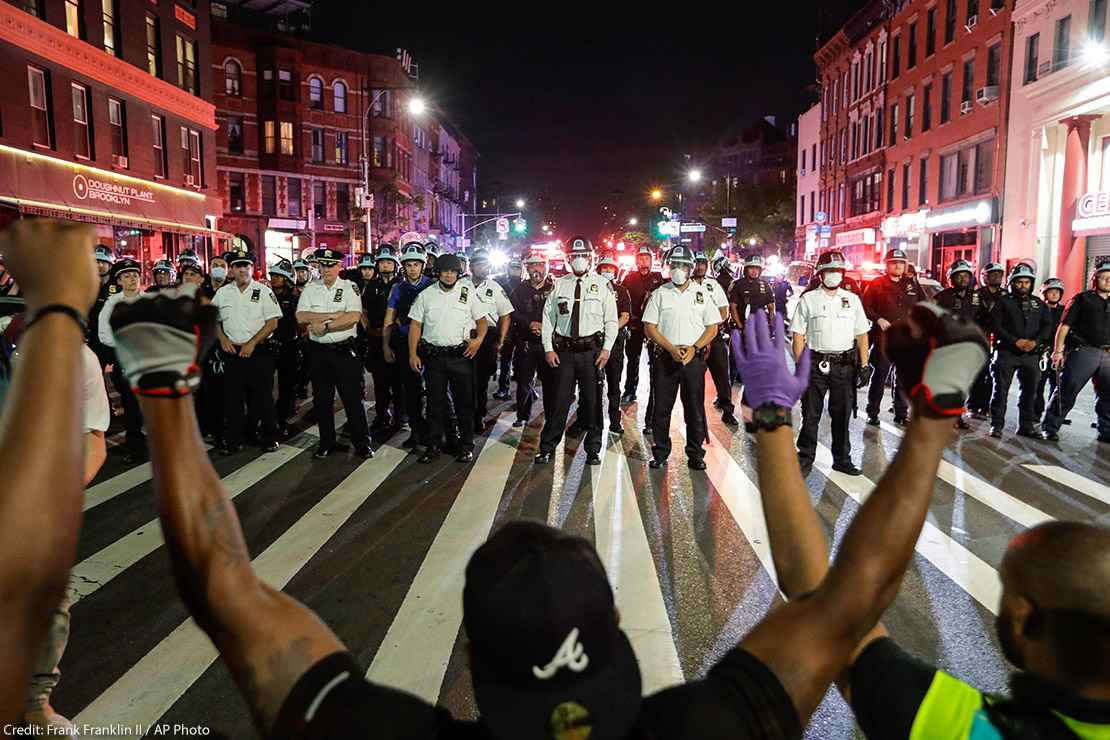 Protesters take a knee on Flatbush Avenue in front of New York City police officers during a solidarity rally for George Floyd