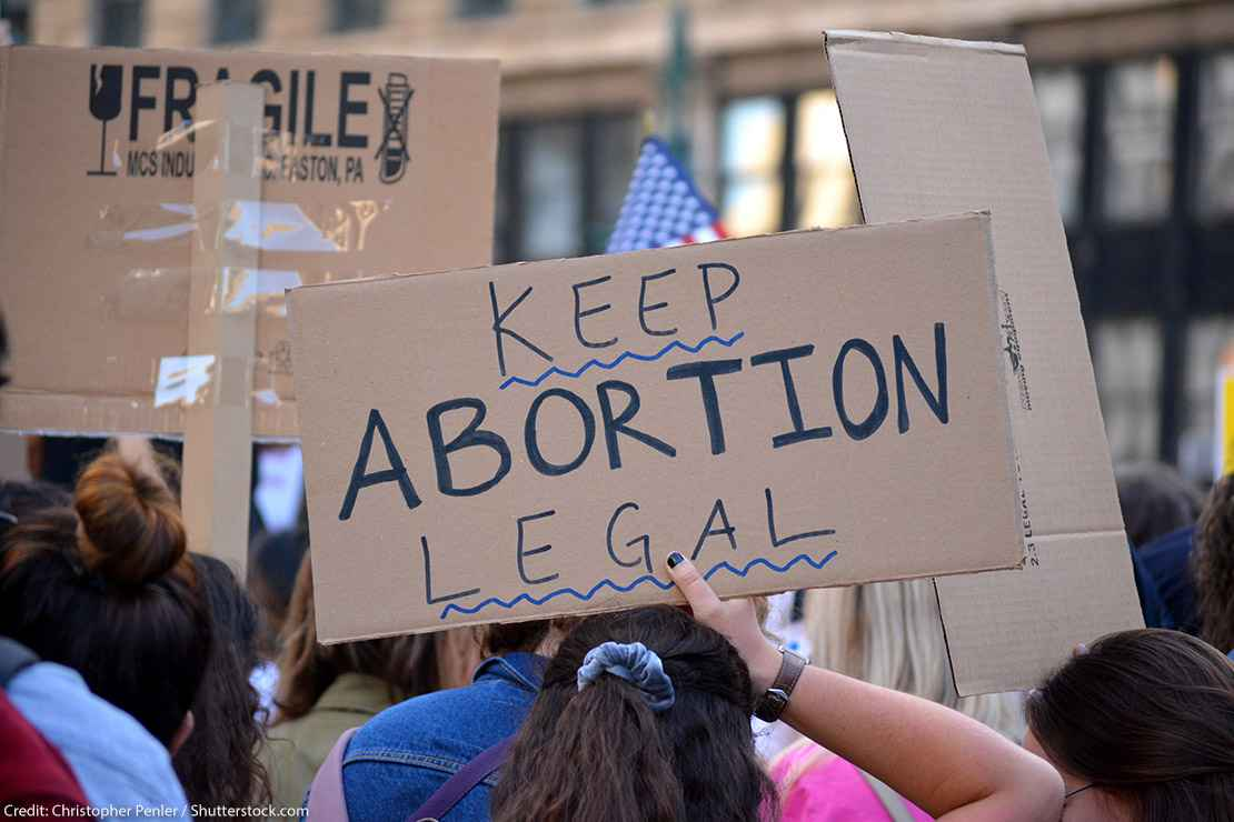 """People protesting in support of abortion rights, holding sign that reads """"Keep Abortion Legal"""""""
