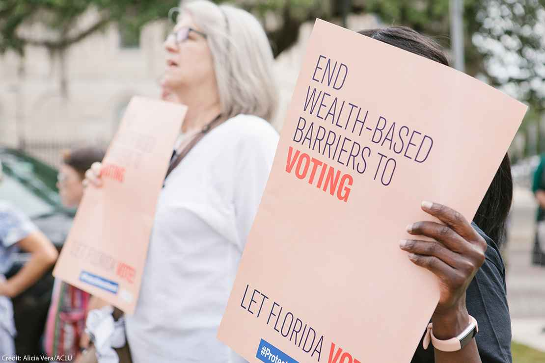 """Woman holding sign reading 'End wealth based barriers to voting"""""""