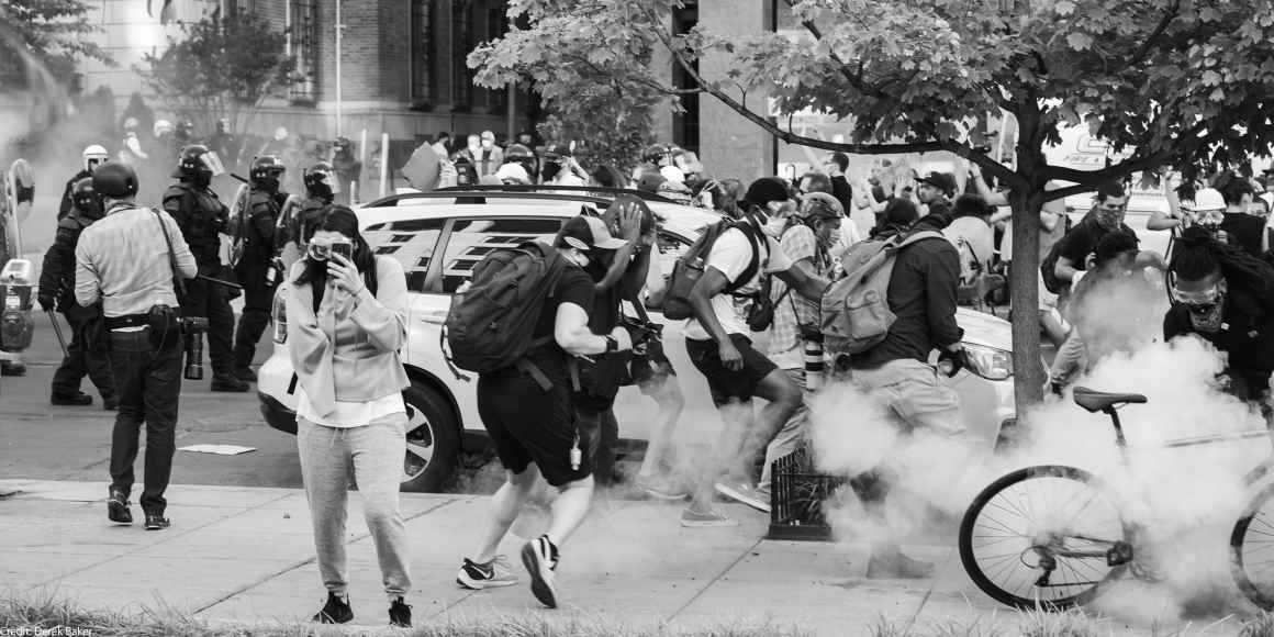 Black Lives Matter Protestors run as tear gas is dispensed into the crowd.