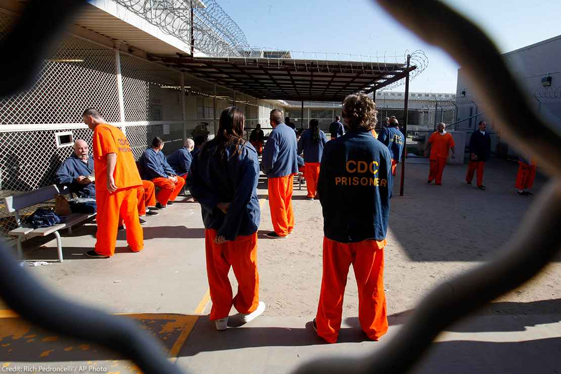 Inmates walk around a recreation yard of a California prison.