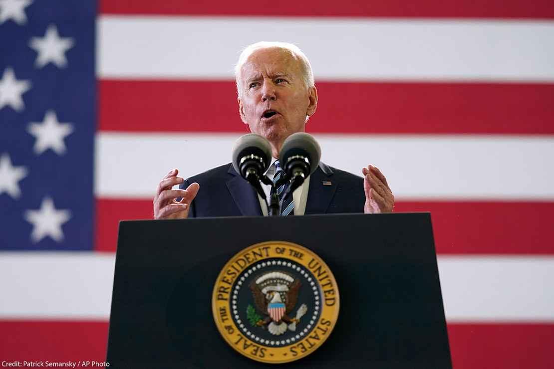 President Joe Biden speaks behind podium to American service members in England