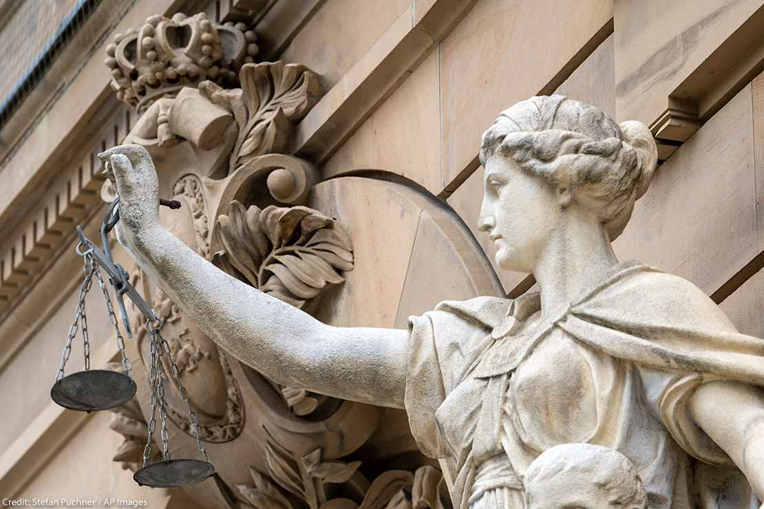 A statue of the goddess Justitia holds a pan of scales in front of the building of the district and regional court.