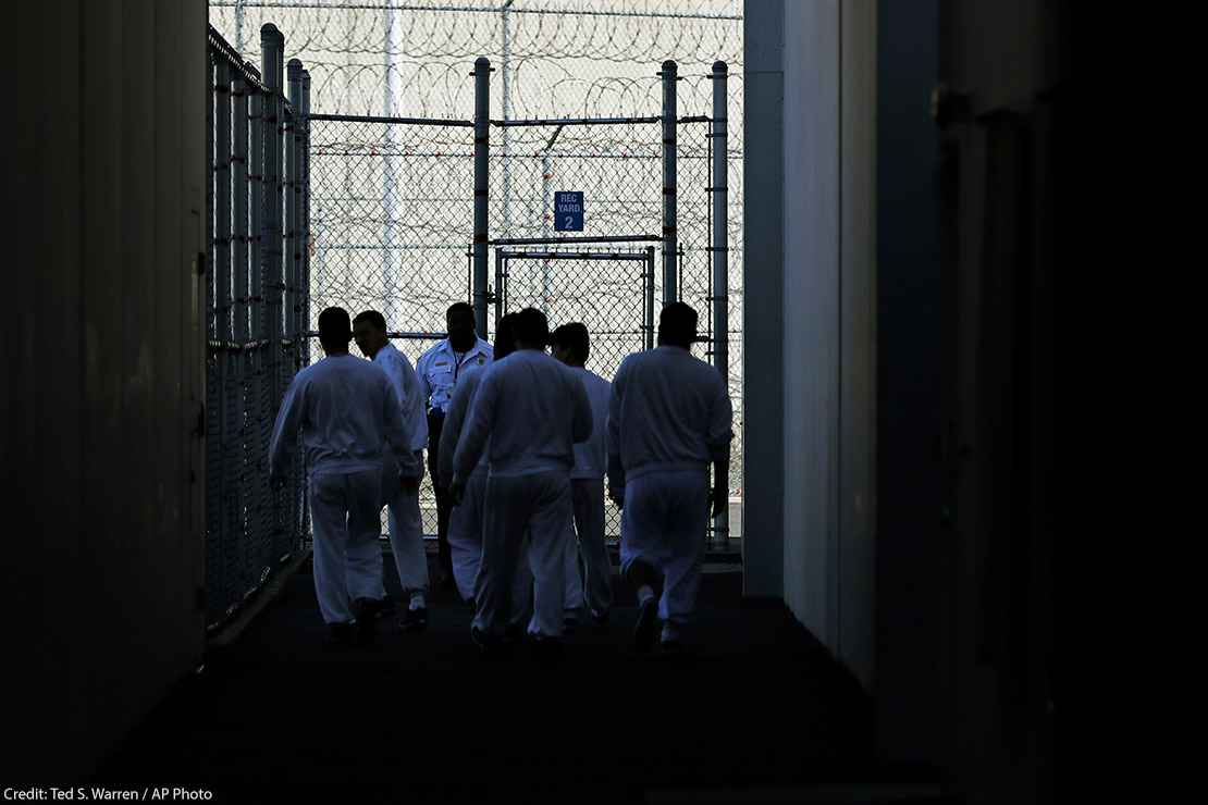 Detainees walk toward a fenced recreation area inside of an ICE detention facility in Washington state.