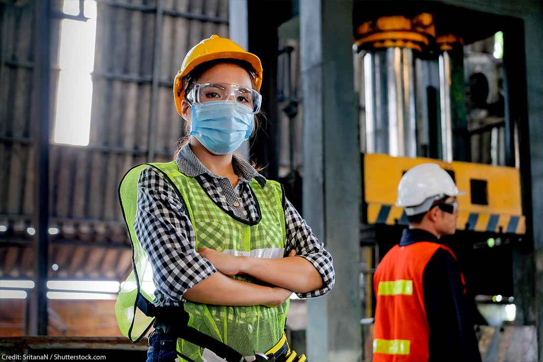 A technician wearing a surgical mask and hard hat stands with arms crossed in a factory.