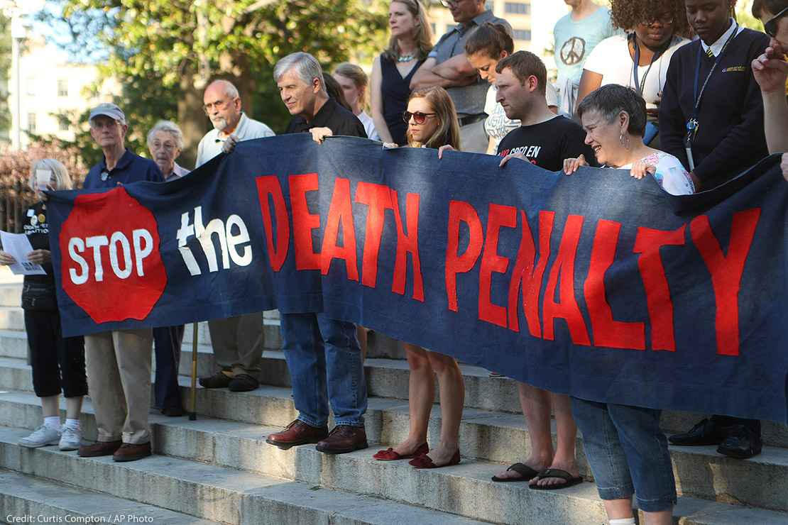 "Protestors holding a banner that reads ""Stop the Death Penalty"" in front on Georgia's State Capital on a sunny day in 2017. Colorado just won a major feat for anti-death penalty movement with its decision to repeal the death penalty in the state."