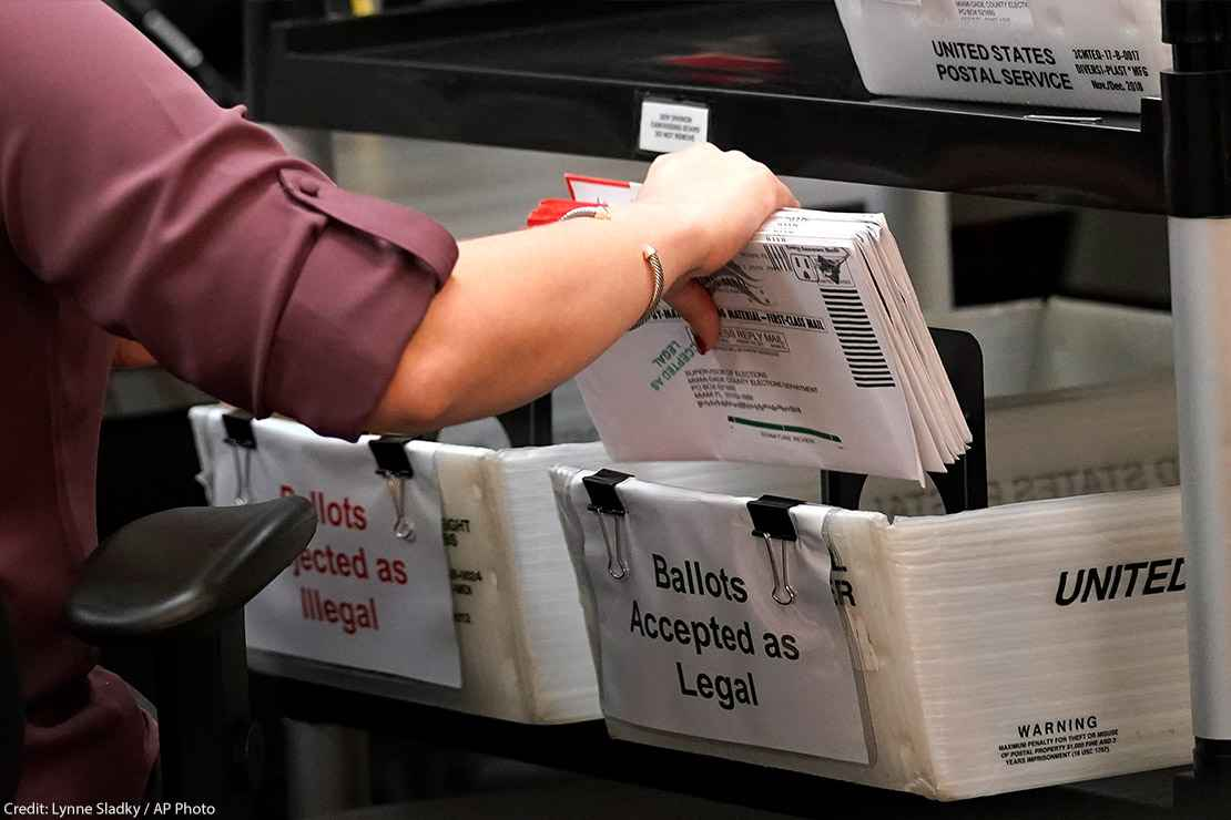 An election worker sorts vote-by-mail ballots in bins.