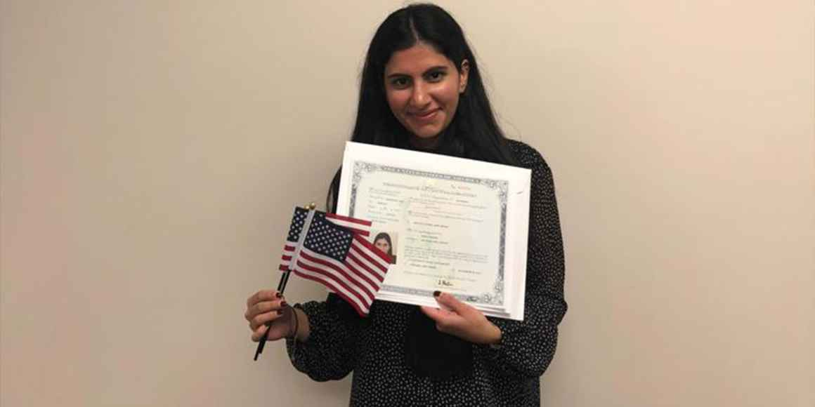 Mira Naseer, a diversity visa recipient, holding her naturalization papers and two American flags.