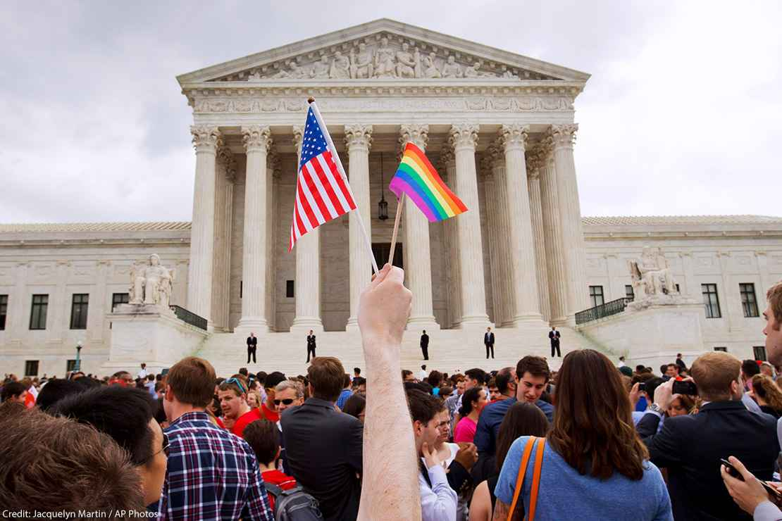 Person holds a mini-American flag and mini-rainbow flag outside of the Supreme Court.