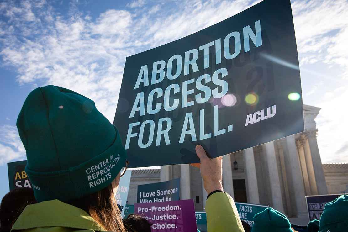 """Person holds up ACLU sign that reads """"Abortion Access for All"""" in front of the Supreme Court building."""
