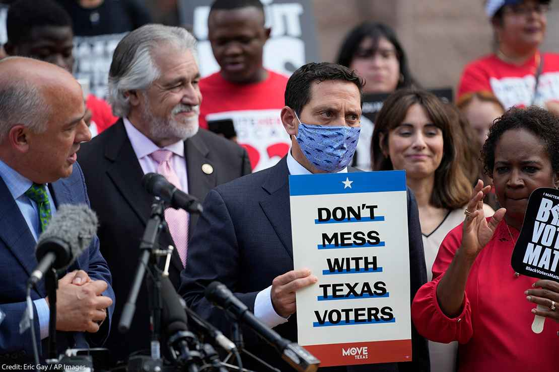 """Rep. Trey Martinez Fischer, D-San Antonio, holds a sign that says, """"Don't mess with Texas,"""" as he and other Democratic caucus members join a rally on the steps of the Texas Capitol to support voting rights"""