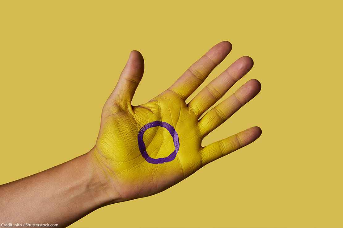 A closeup of the intersex flag painted on the palm of a person's hand.