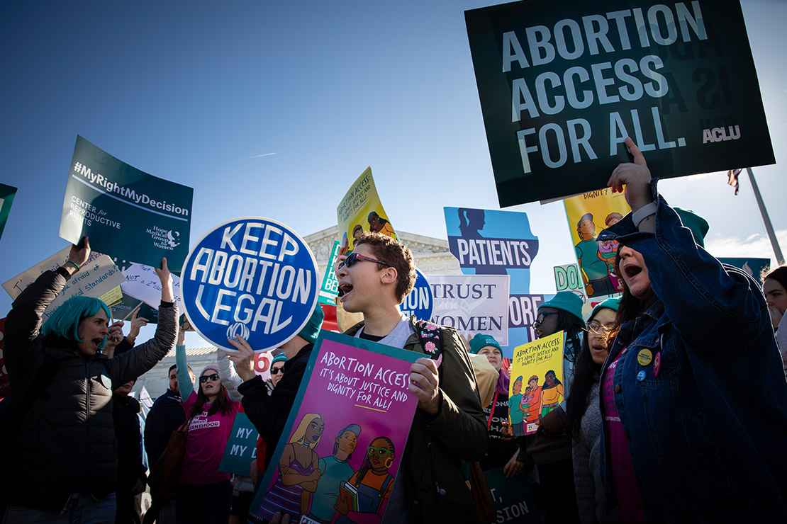 "Abortion activists hold signs at rally that read"" Keep Abortion Legal"" and ""Abortion Access for All."""