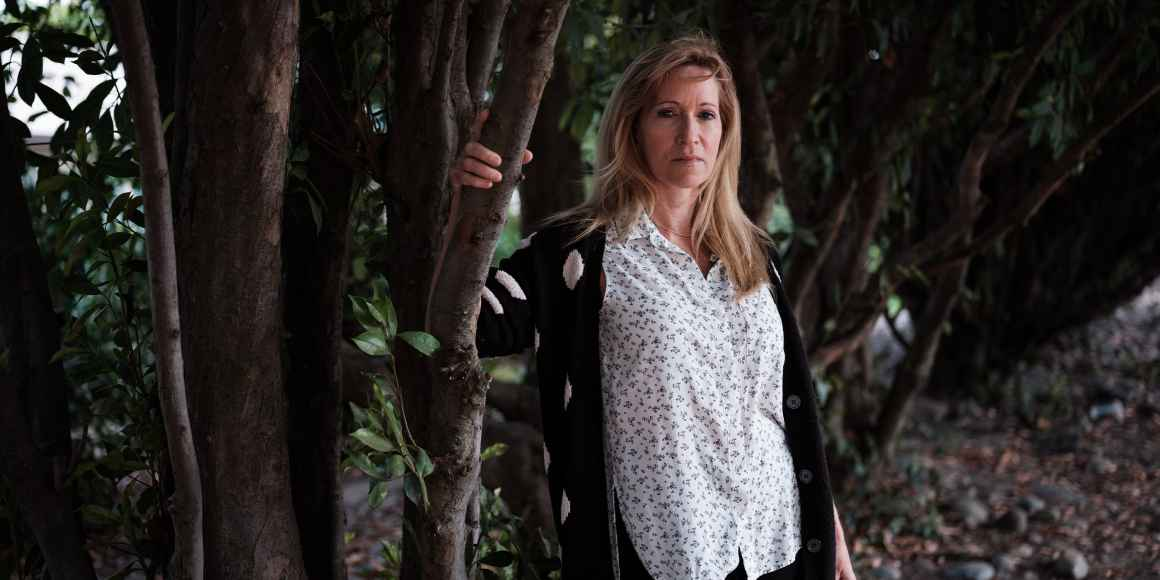Kristen DiAngelo, sex worker and activist, in white shirt standing with arm on a tree branch