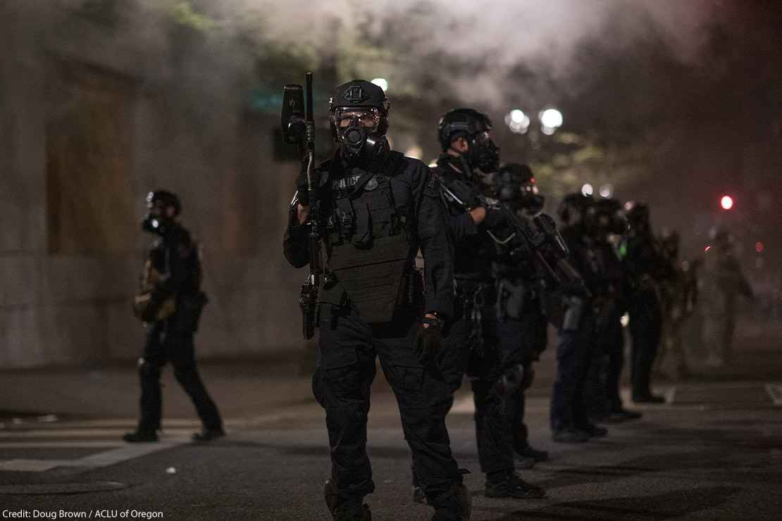 Police in Portland wear riot gear and armed with guns as smoke fills the streets.