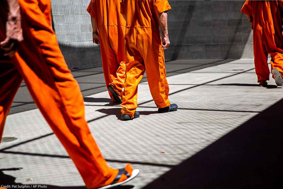 inmates walk the yard during recreation time in a county jail.