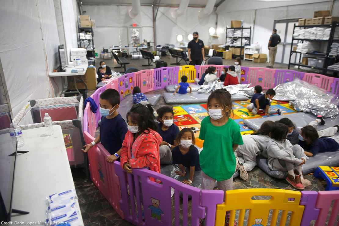 young unaccompanied migrants, from ages 3 to 9, watch television inside a playpen at the U.S. Customs and Border Protection facility
