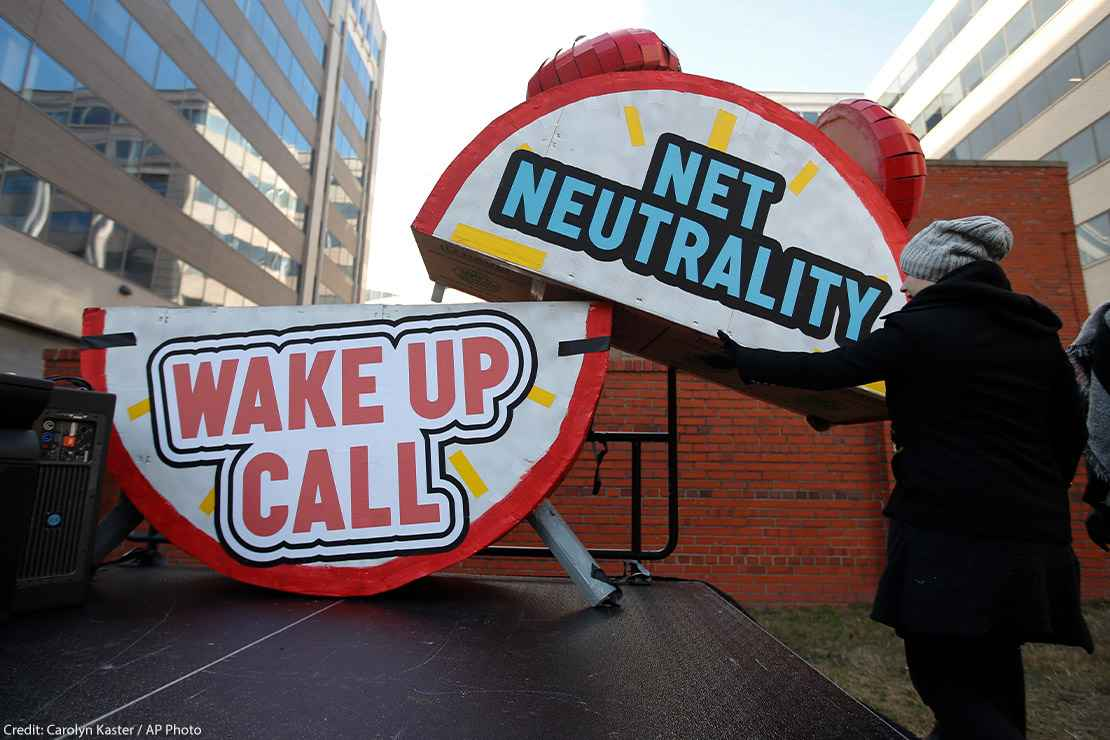 """Woman helps to dismantle a large alarm clock display that reads """"Net Neutrality Wake Up Call"""" from the stage after a protest in front of the FCC in Washington, DC."""