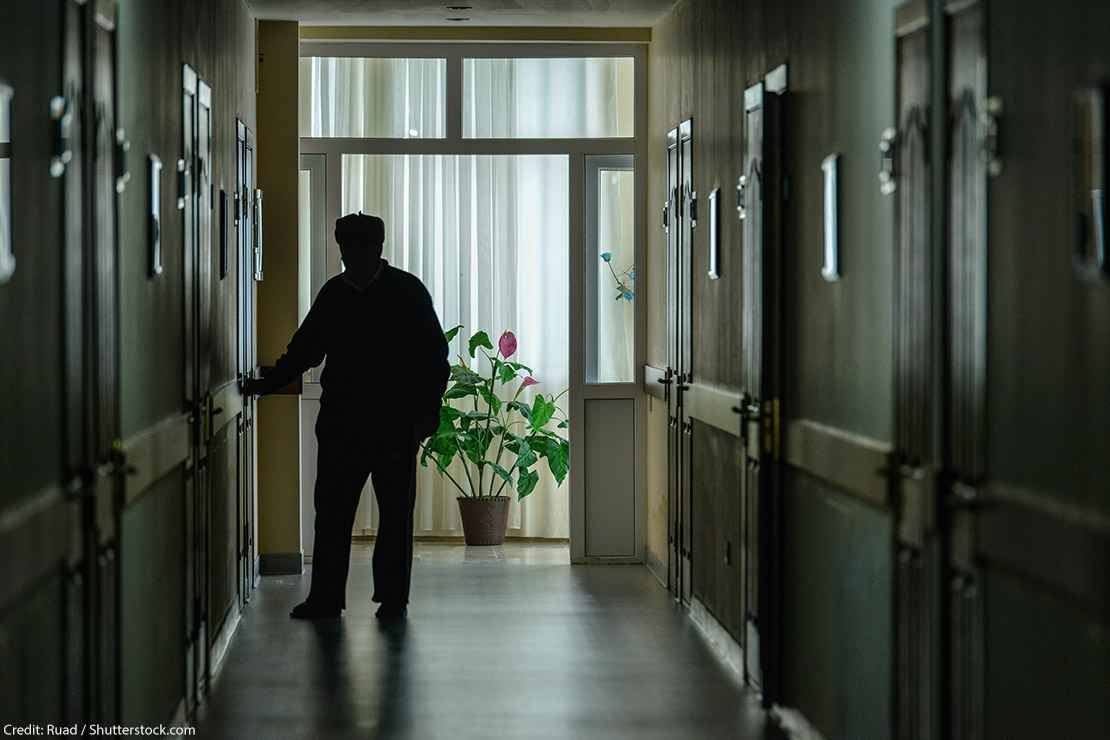 A resident walks down the darkened hall of a nursing home.