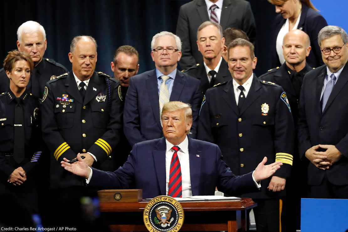 President Trump sits at podium ready to sign executive order creating a commission to study law enforcement and justice, surrounded by officers beside him in support.