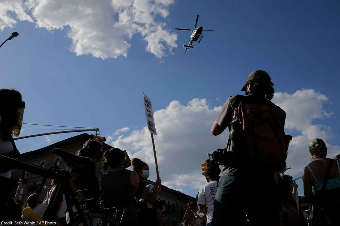 Protestors react to a low flying helicopter during a march in Brooklyn, New York.