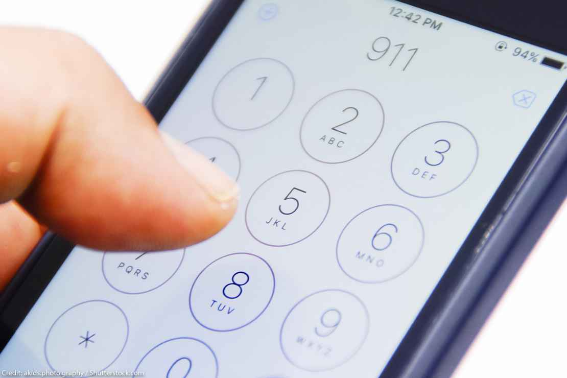 Hand holding smartphone with emergency number 911 on the screen.