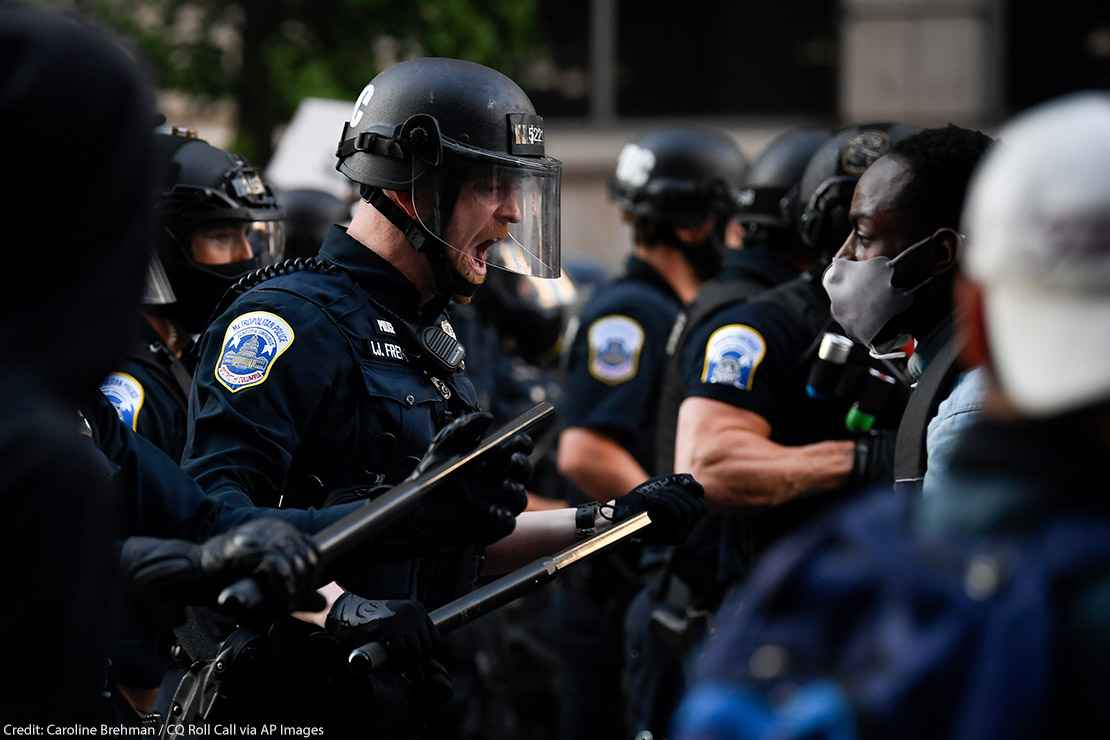 Police in riot gear shouts in black protestor's face as demonstrators gather to protest the death of George Floyd near the White House