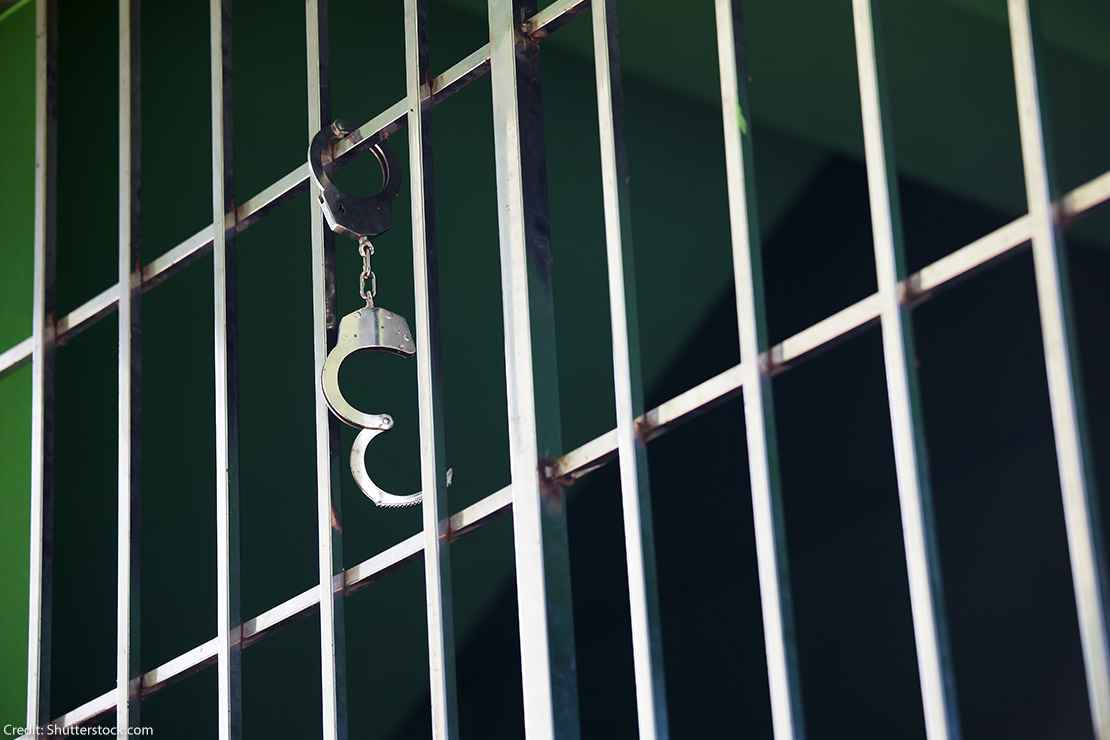 Handcuffs hanging from jail cell.
