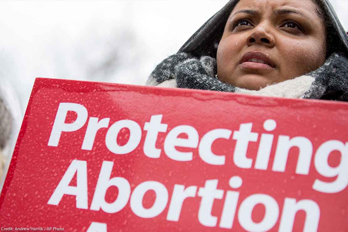 """A woman holds a """"protecting abortion access"""" sign in the rain."""