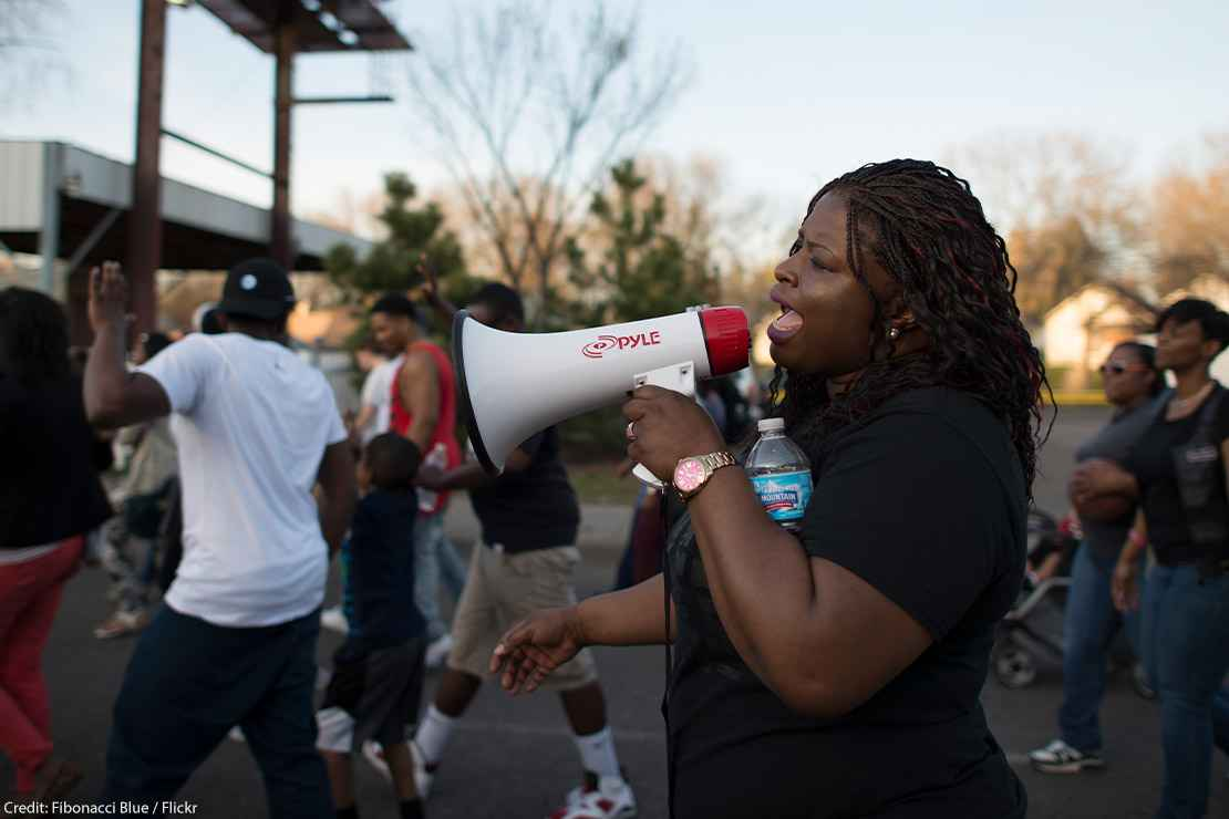 A Black woman using a megaphone at a daytime Black Lives Matter march in Minneapolis, Minnesota in response to police shooting of 18-year-old Tania Harris.