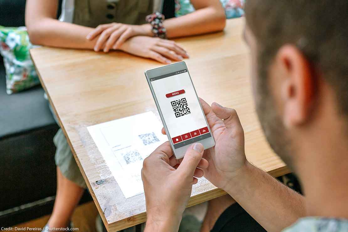 A man uses his phone to scan restaurant QR code on table