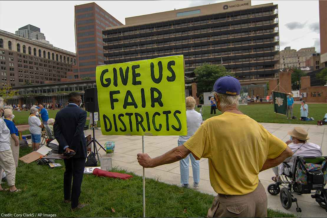 """Man holding sign that says, """"Give us fair districts."""""""