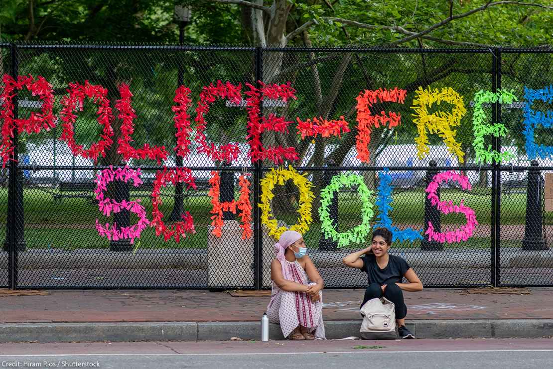 """A sign made out of confetti that reads """"Police Free Schools"""" on a gate during a Black Lives Matter protest."""