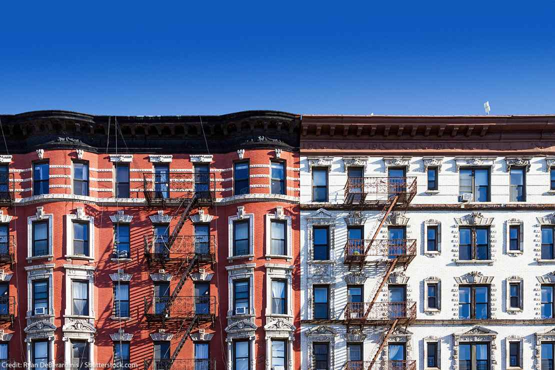 New York City block of old historic apartment buildings in the East Village of Manhattan, with clear blue sky background.