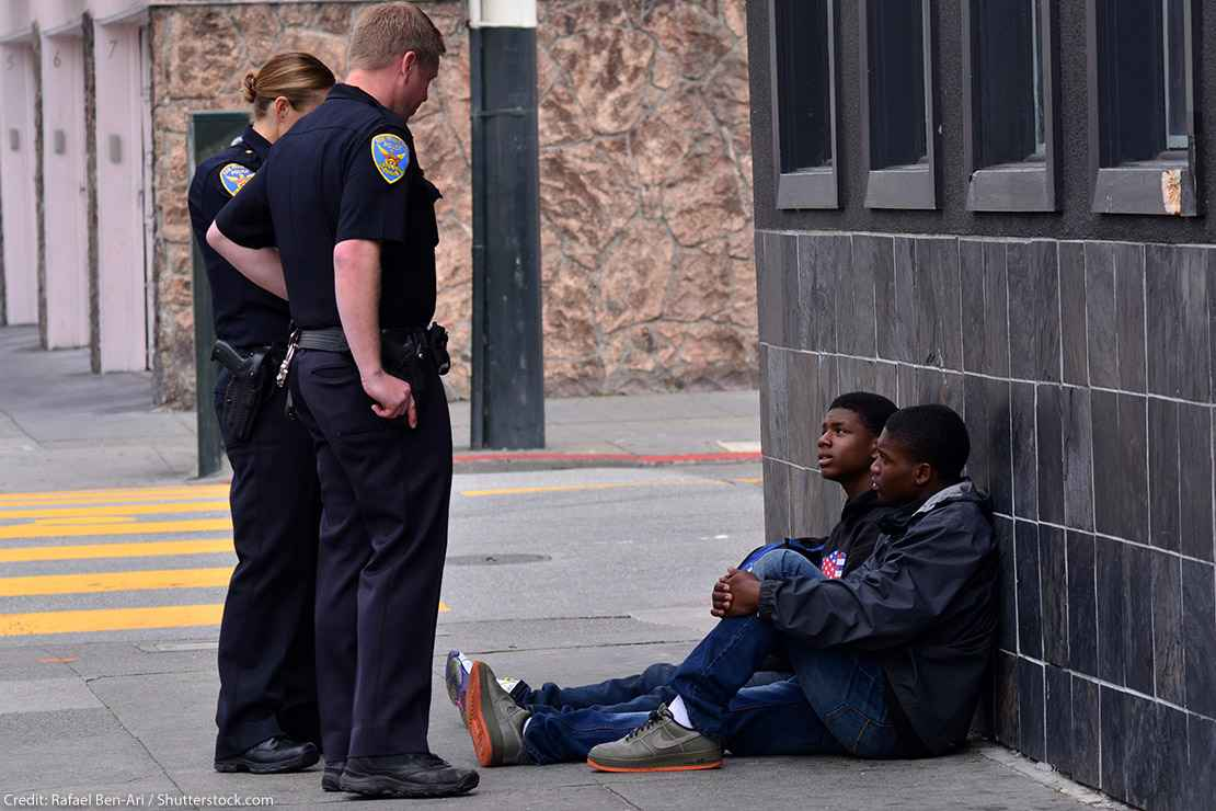 Two San Francisco police officers interrogating and standing over two Black American men seated on the sidewalk. Overall, Black Americans are arrested at 2.6 times the per-capita rate of all other Americans.