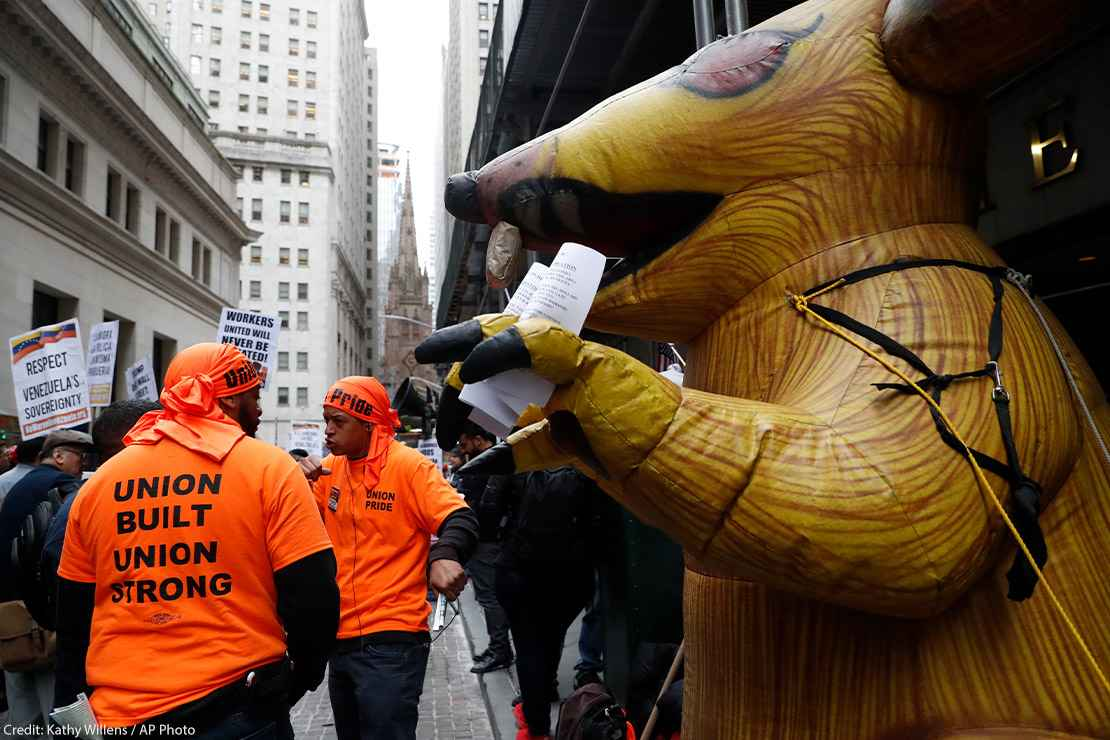 A giant inflatable rat stands in front of a non-union worksite where union workers protested during a May Day rally