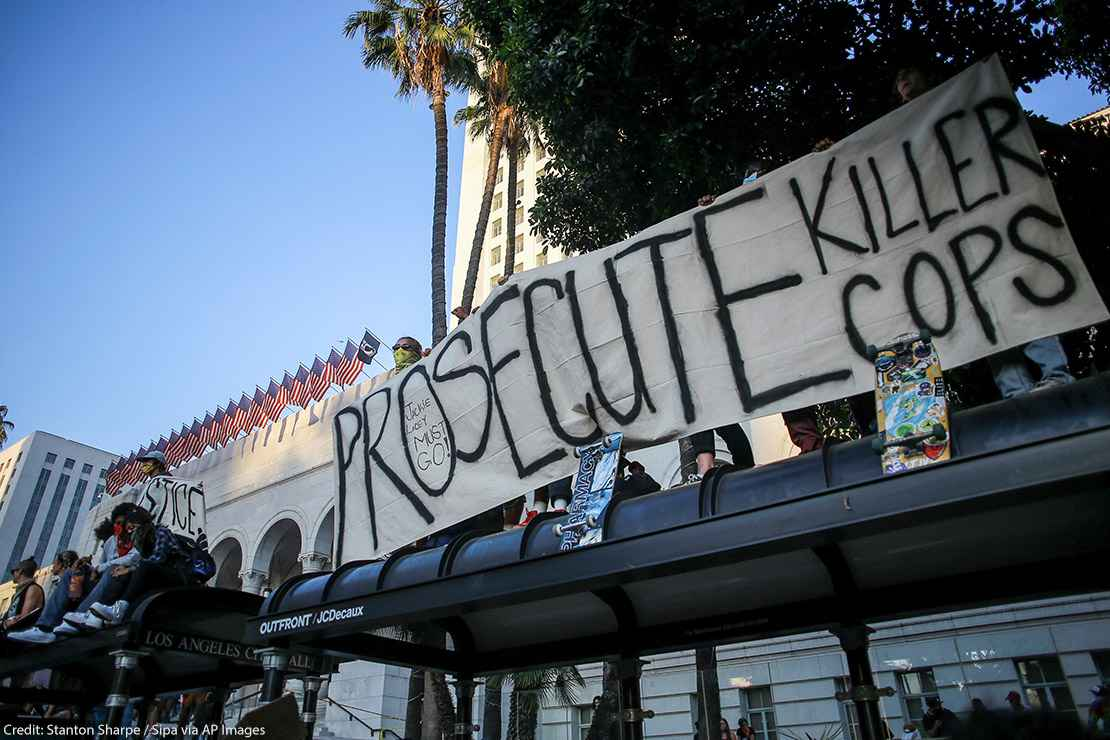 """Protesters hold a banner that says, """"Prosecute Killer Cops"""" in front of Los Angeles City Hall during the demonstration."""