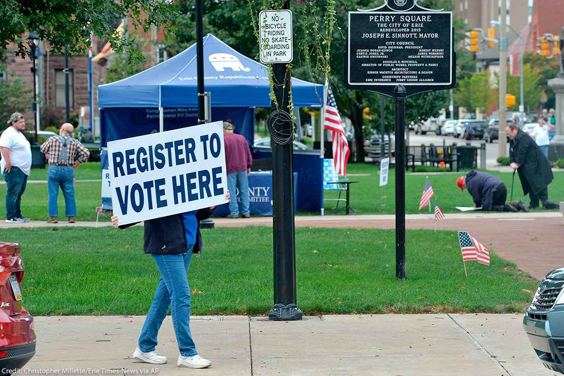 """Person holds sign that reads """"register to vote here"""" near a voter registration booth on a Pennsylvania street"""