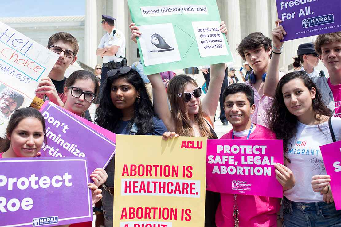 Pro-choice demonstrators with signs advocating the protection of the right to a safe abortion and that abortion is healthcare.
