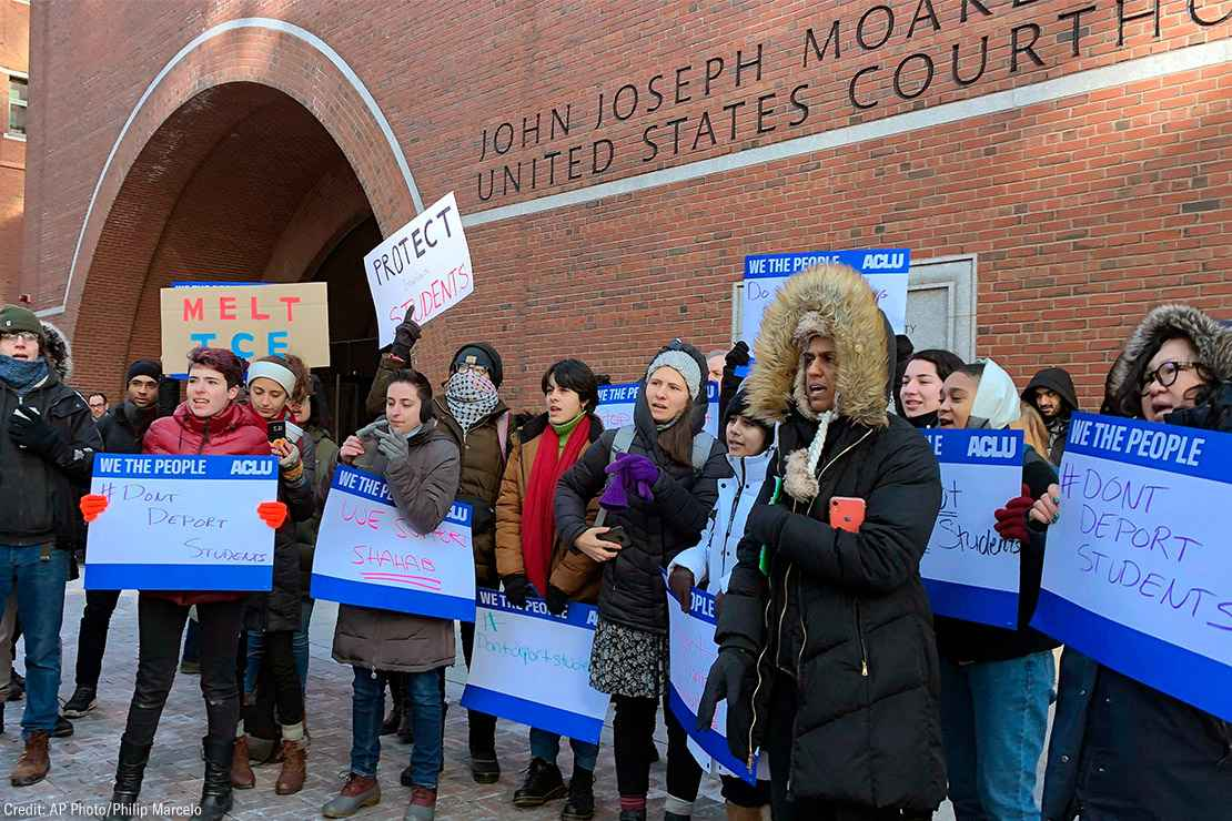 Protesters stand outside the federal courthouse where a hearing was scheduled for Northeastern University student Shahab Dehghani