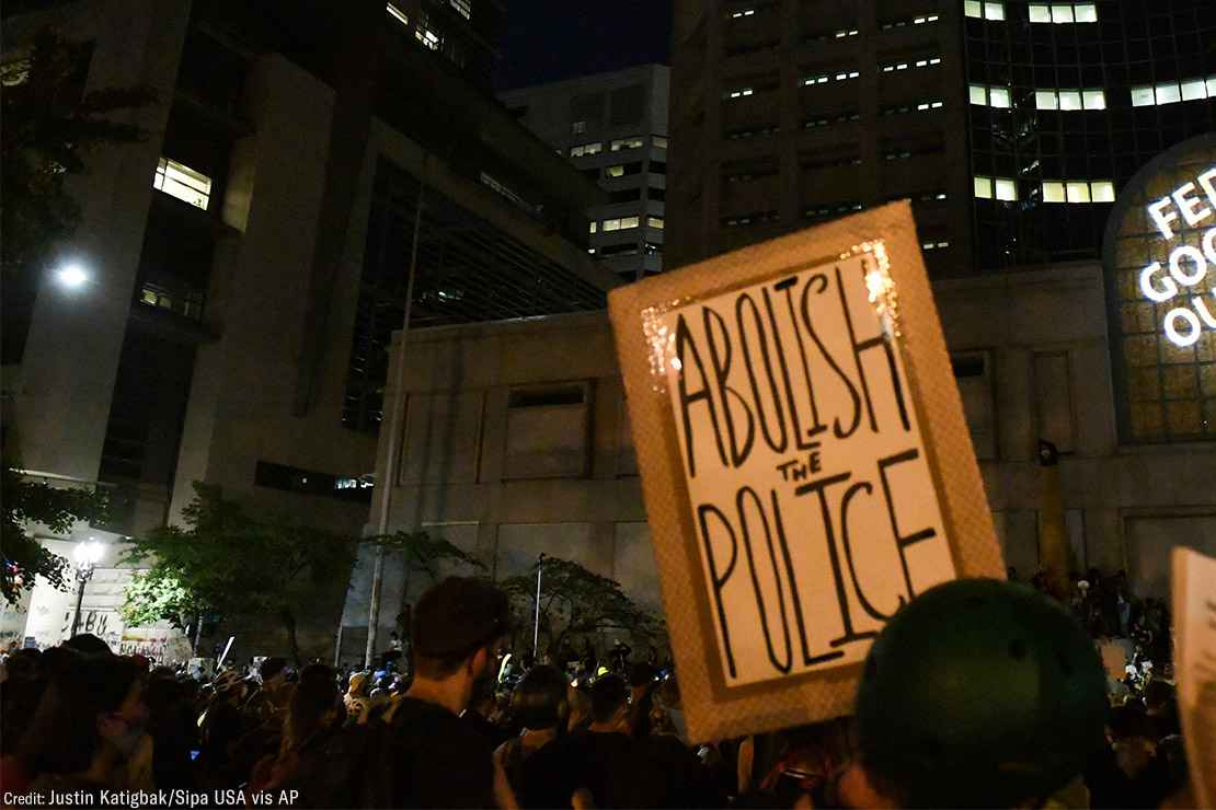 "A group of protesters with one holding a sign with the text, ""Abolish the Police."""