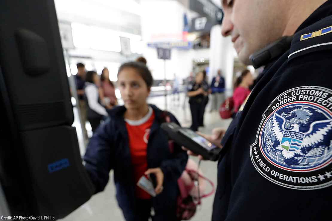 A passenger using a facial recognition kiosk in the background with a U.S. Customs and Border Protection officer watching in the foreground.