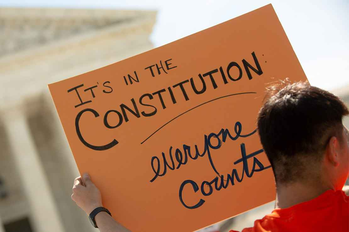 """A demonstrator holding a sign with the text """"It's in the Constitution: everyone counts"""" outside the Supreme Court."""