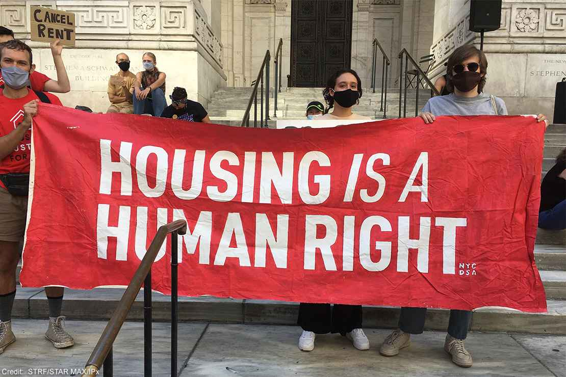 """Protesters carrying a banner with the text """"housing is a human right."""