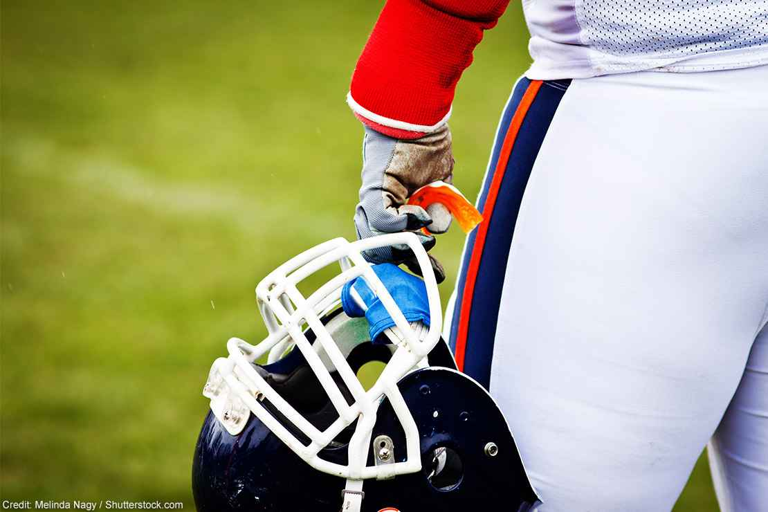 A football helmet in a player's hand.