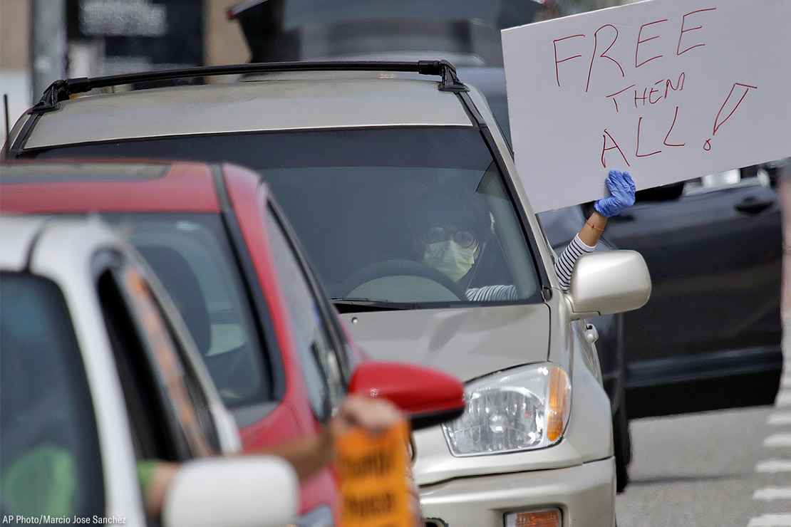 """A demonstrator holds a sign with the text """"Free Them All"""" in a car-based protest to demand the release of immigrants in California detention centers over COVID-19 concerns."""