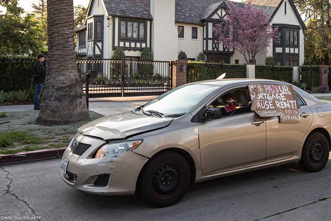 A protestor drives by L.A. Mayor Eric Garcetti's mansion with a sign in favor of extended rent and mortgage protections.