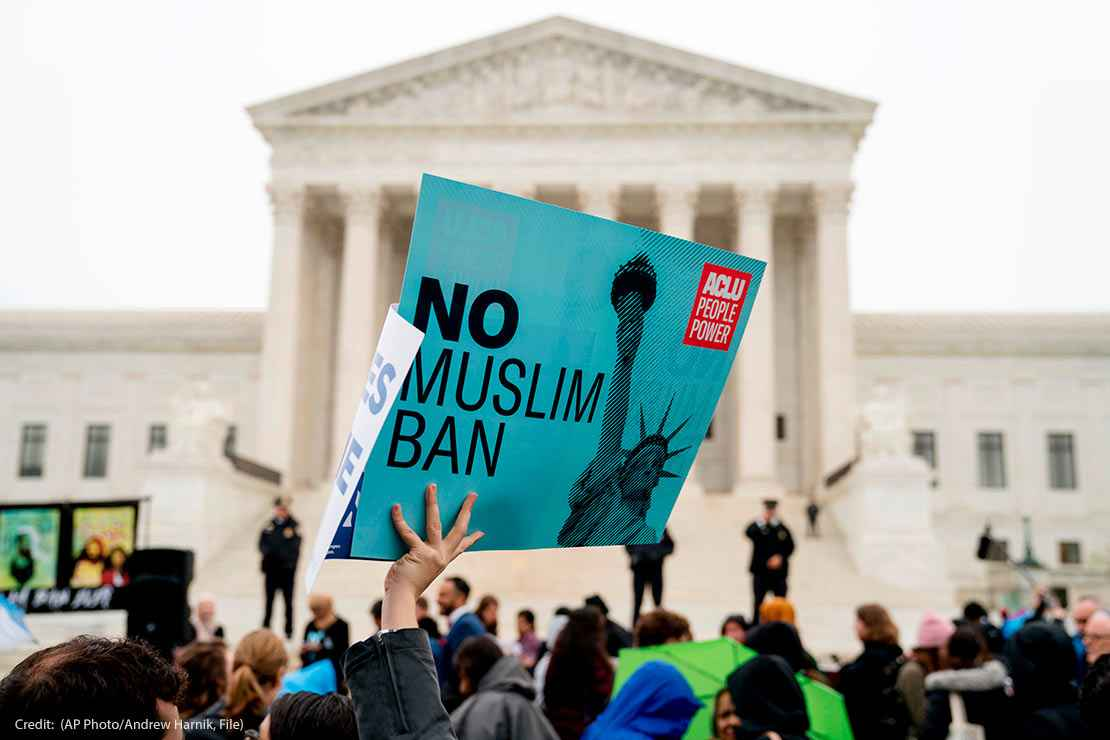 "In this April 25, 2018 photo, a person holds up a sign that reads ""No Muslim Ban"" during an anti-Muslim ban rally at the Supreme Court"