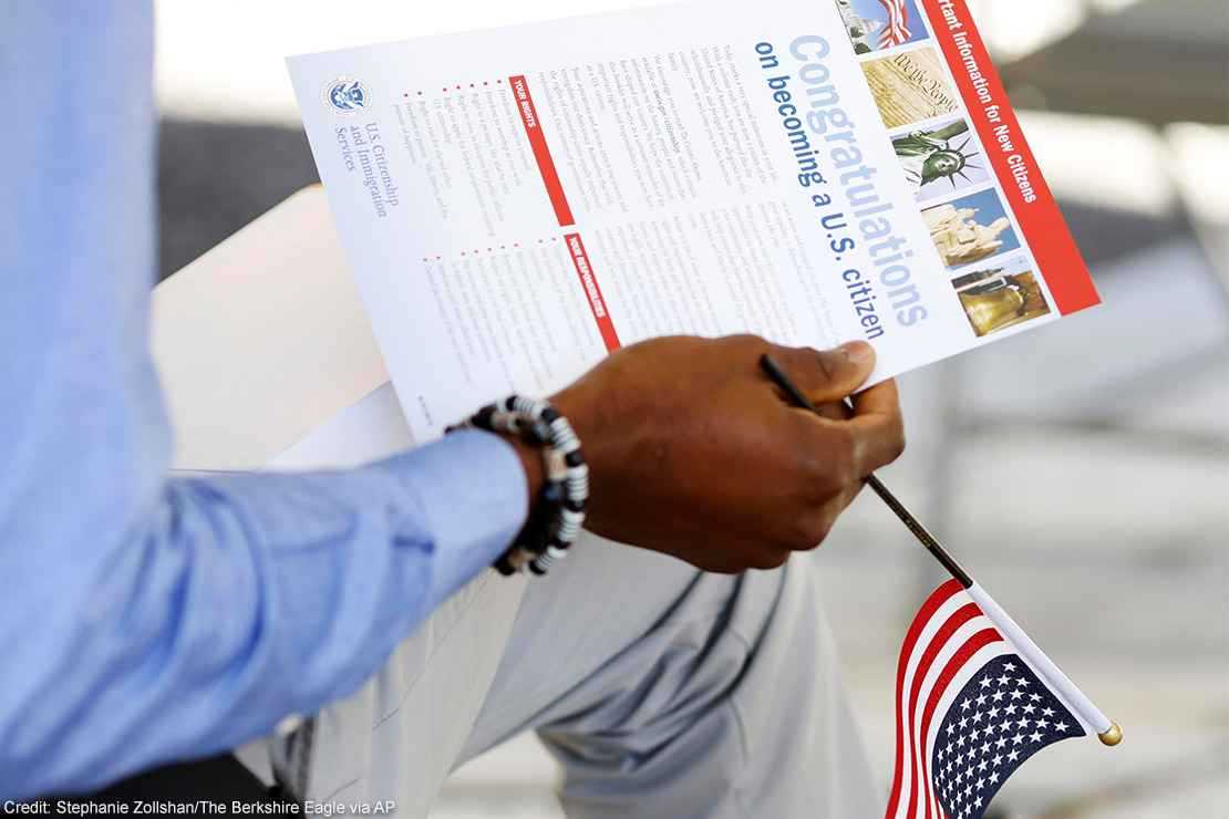 The hand of a seated person holding a miniature U.S. flag and immigration information at a naturalization ceremony.